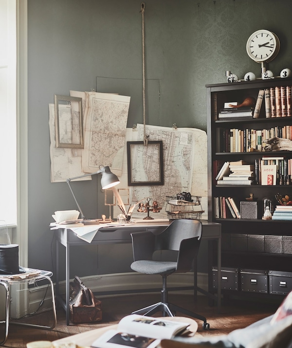 A desk and chair in the corner of the living room, with maps and frames on the wall and an IKEA HEMNES bookcase.
