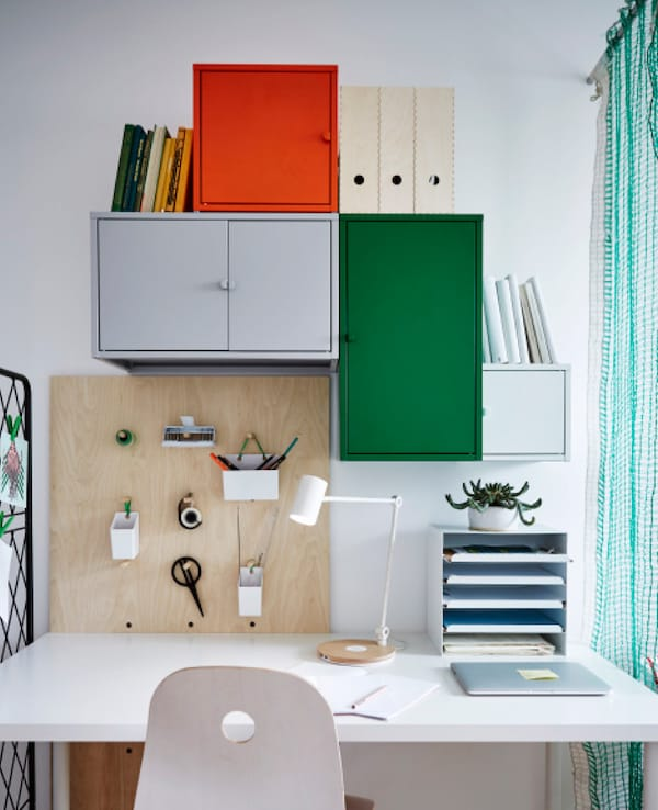 A desk area with lots of storage and a peg board.
