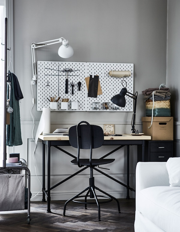 A desk at the side of a living room with crafting accessories on a pegboard.
