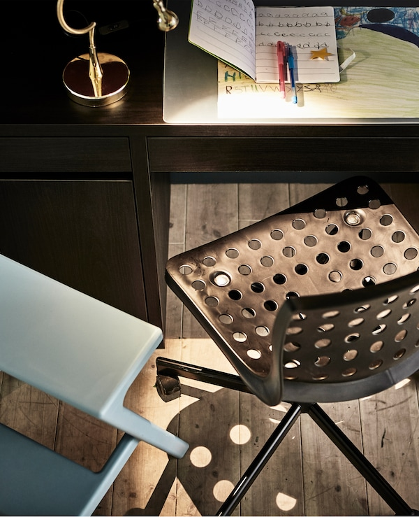 A desk chair for a child and a stool for their parent sit in front of a desk.