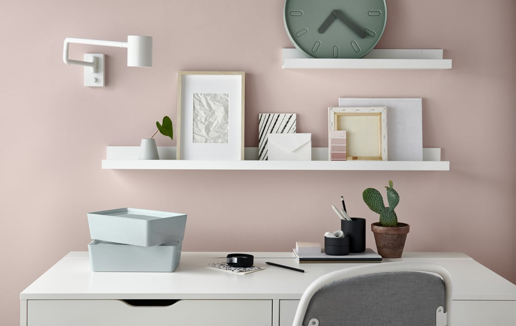 A desk, drawer and chair in a home office set against a wall decorated with big splatters of different coloured paint.
