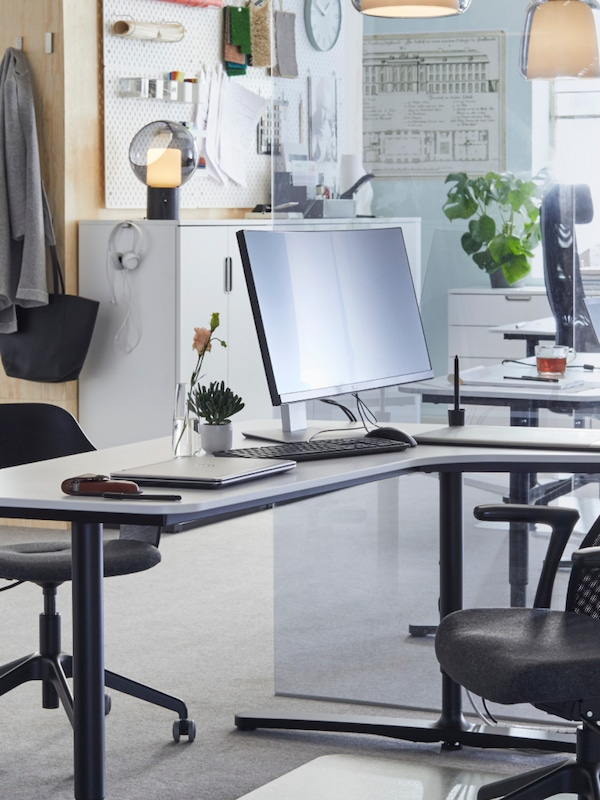 A desk in an office with a computer and a chair on the foreground