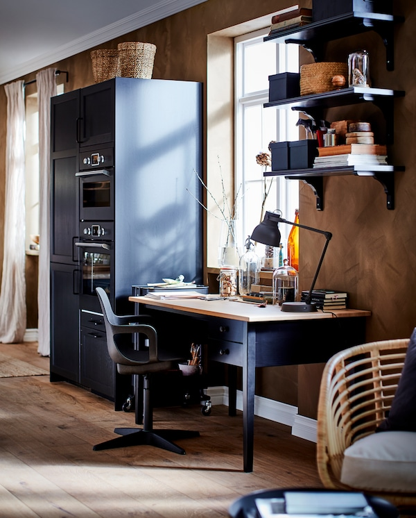 A desk in black/solid pine, a swivel chair, wall shelves in black-brown and a black kitchen section with drawers and doors.