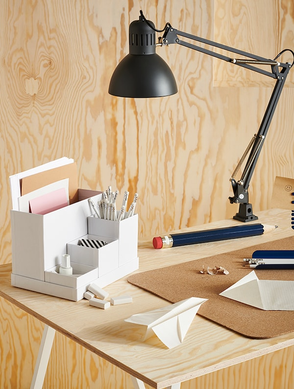 A desk lamp pivoted towards the center of a desk, with items sitting on top including a pencil, paper plane and more.