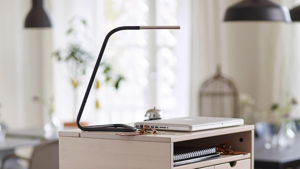 A desk lamp sitting on a small desk