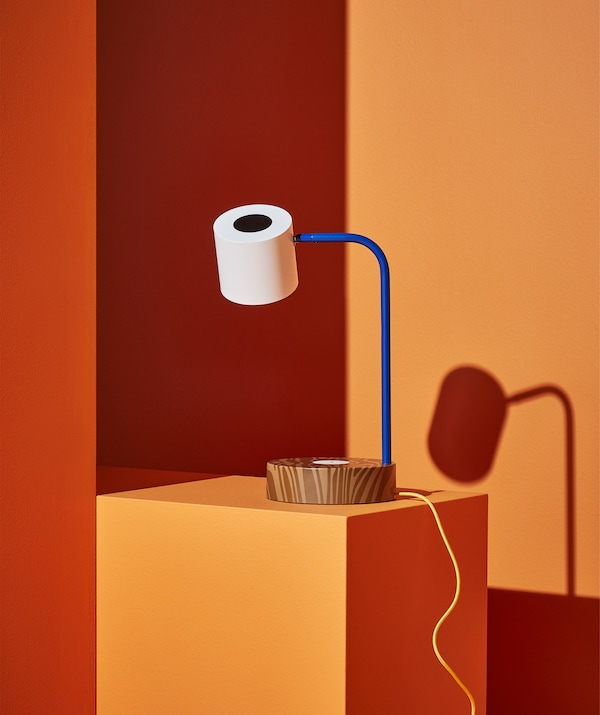 A desk lamp with brown base, blue stand and white shade, on an orange step.