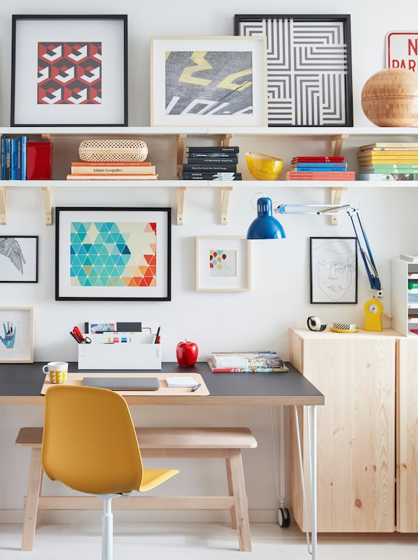 A desk on castors stands by a wall, surrounded by a TERTIAL work lamp, wooden cabinets, wall shelves, and framed artwork.