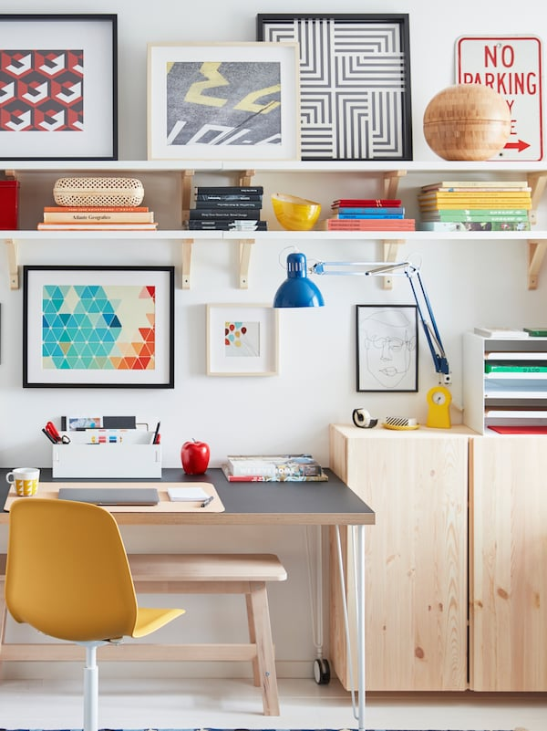 A desk on castors stands by a wall, surrounded by light-wood IVAR cabinets, wall shelves, and framed artwork.