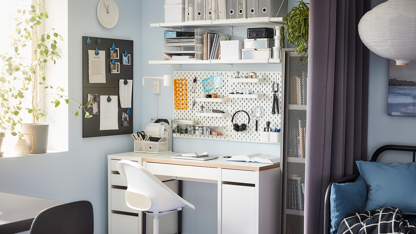 A desk, swivel chair, wall-mounted shelf and a pegboard in white, a grey cabinet and a window.
