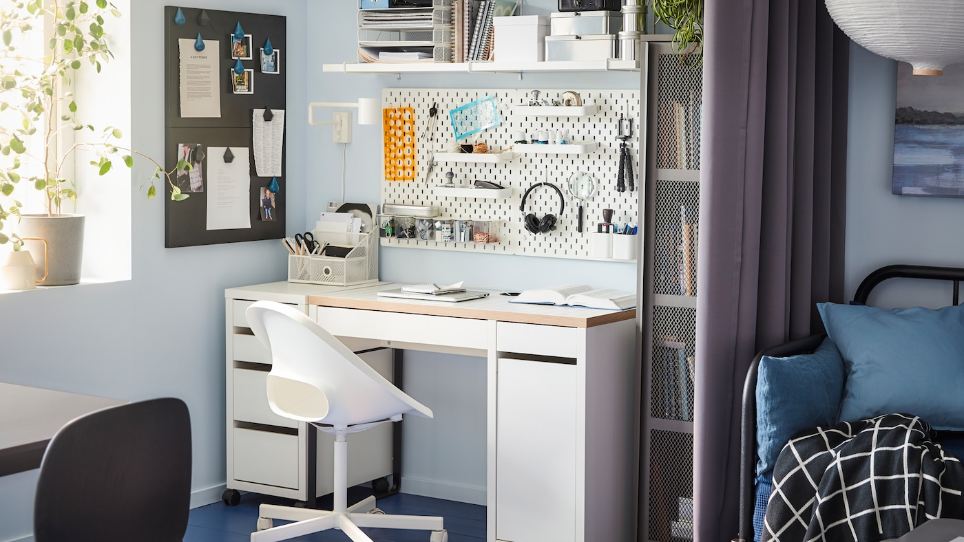 A desk, swivel chair, wall-mounted shelf and a pegboard in white, a gray cabinet and a window.