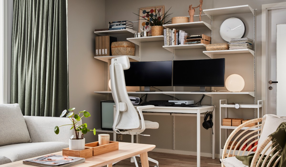 A desk, swivel chair, wall-mounted shelving system, by a window.