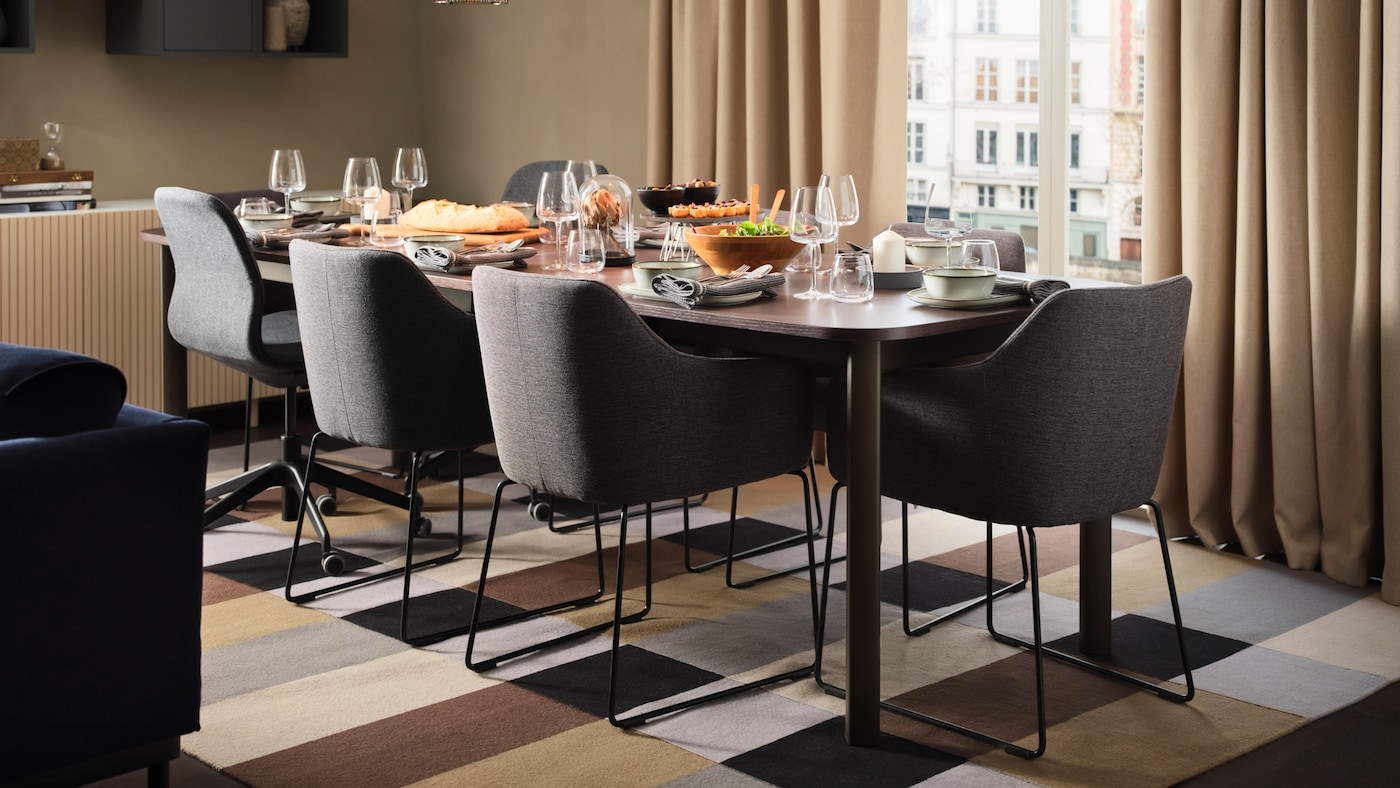 A dining area by a window with a large dining table, six metal black/grey TOSSBERG chairs and two dark grey office chairs.