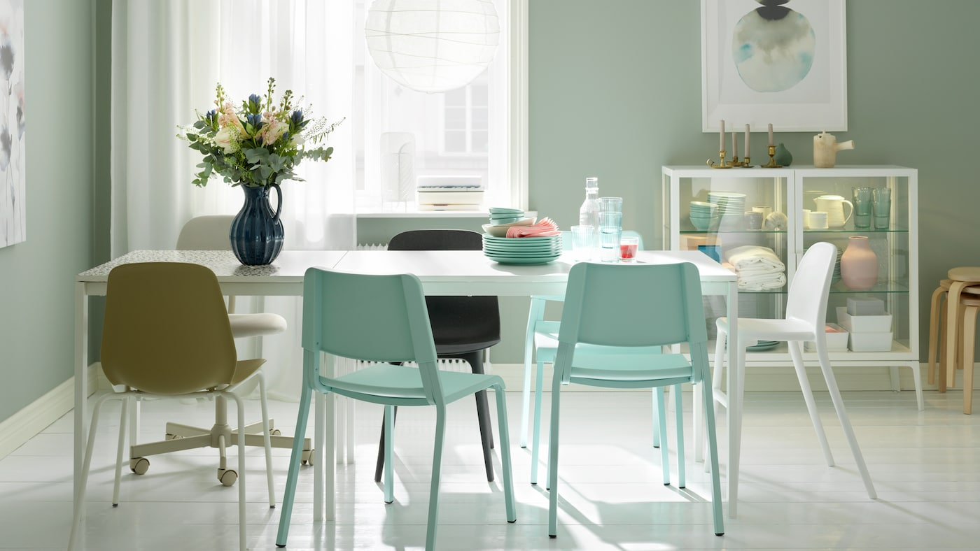 A dining area formed by two white MELLTORP tables in line, a white REGOLIT lamp, assorted chairs and flowers in a vase.