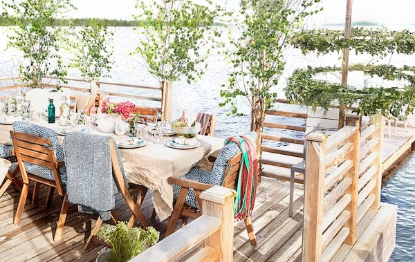 A dining area set for a party sits on a dock in a lake.