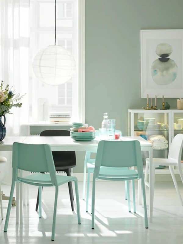 A dining area with a white MELLTORP table, a white REGOLIT lamp and assorted seating.
