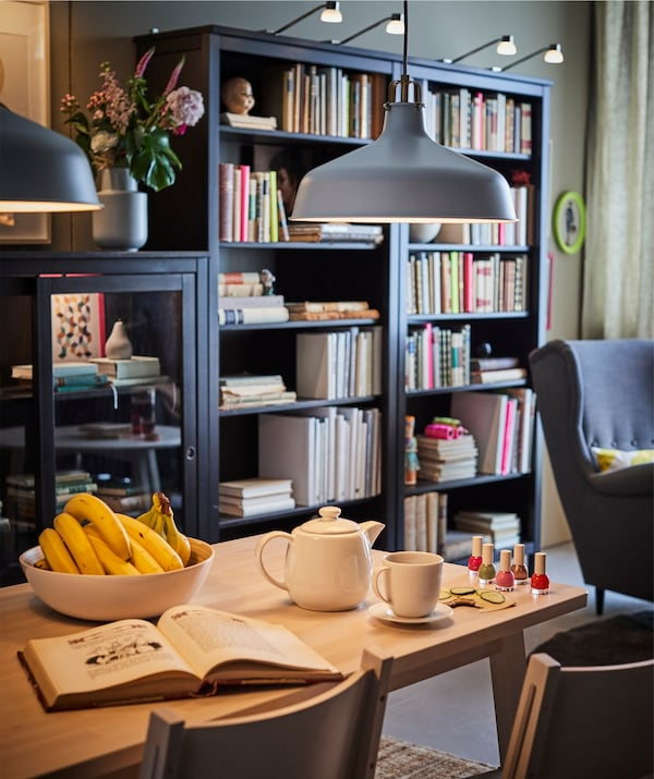 A dining area with an IKEA RANARP pendant lamp illuminating the table, with bookcases behind.