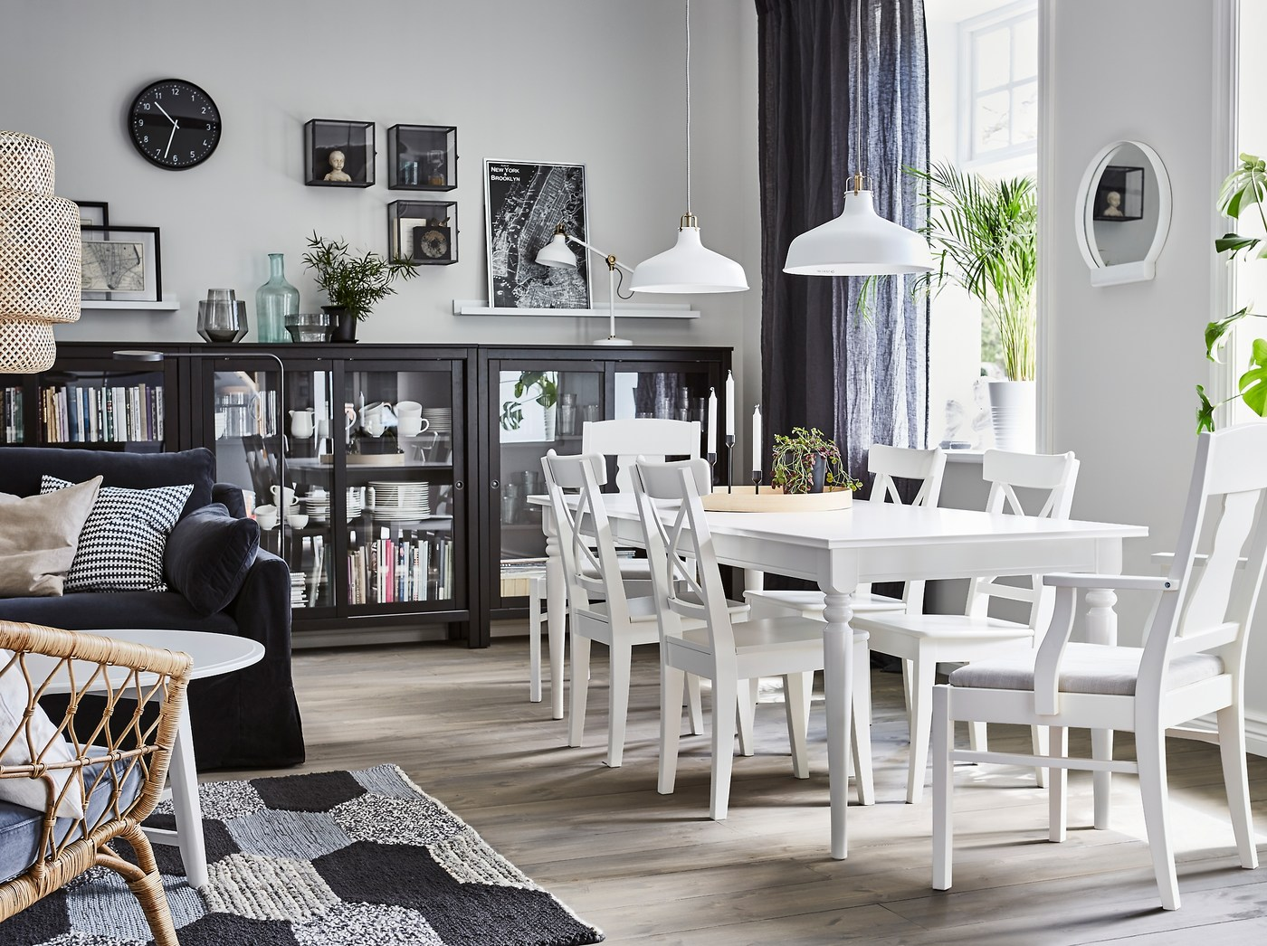 A dining area with white INGATORP extendable dining table and HEMNES black glass door cabinets to store dinnerware.