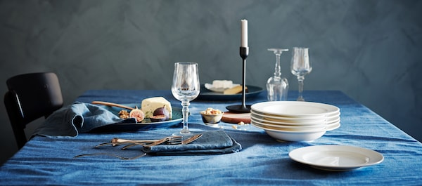 A dining, elegantly table set with KONUNGSLIG wine glass, plates, dishes, a candle stick, some food and a blue table cloth.