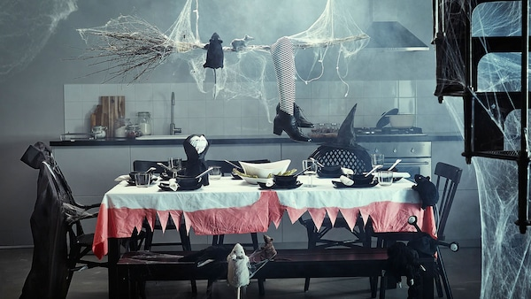 A dining room table decorated with Halloween decorations. Costumes laying over chairs