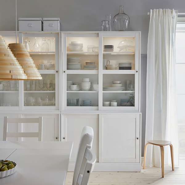 A dining room where dinnerware and glasses are stored inside a white HAVSTA storage combination with sliding glass doors.