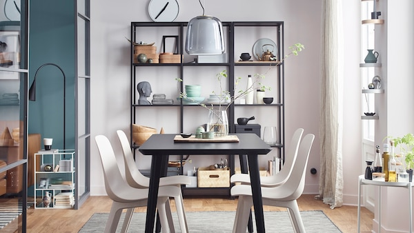 A dining room with a black table and beige chairs, an open cabinet with decorations and a side table with seasonings.
