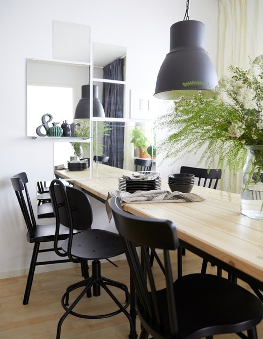 A dining room with a pine table and six black chairs and a wall decorated with mirrors to help create depth in the room.