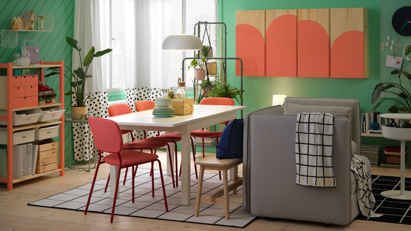 A dining room with a white table, red chairs, and grey sofa and a cabinet and a shelving unit painted in coral colour.