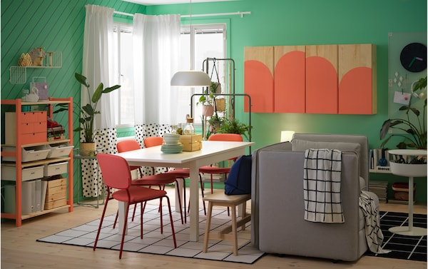 A dining room with a white table, red chairs, and grey sofa and a cabinet and a shelving unit that's painted in coral colour.