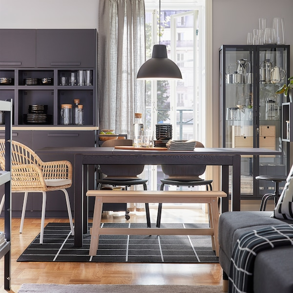 A dining room with an extendable table that's extended. Black chairs, a rattan chair and a bench in birch provide seating.