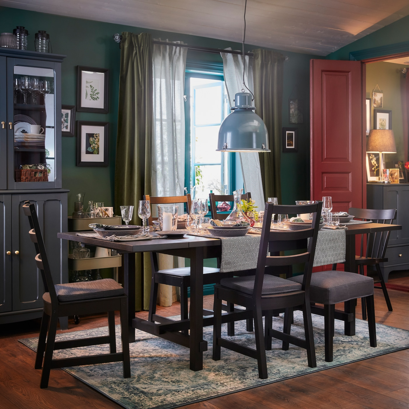 A dining room with an extended table and five chairs in black, an oriental-patterned rug and a grey-turquoise pendant lamp.