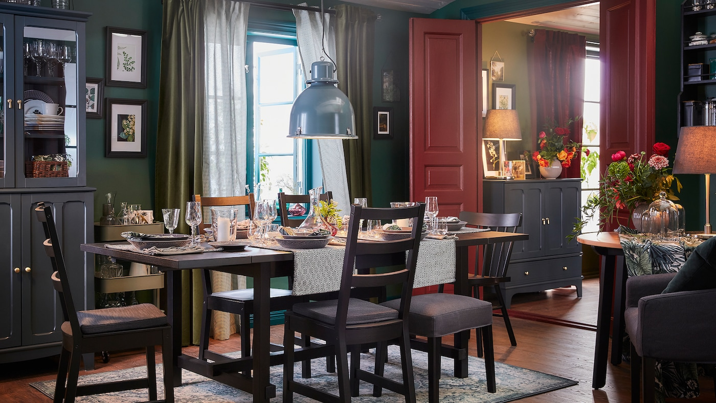 A dining room with an table and five chairs in black, an oriental-patterned rug and a gray-turquoise pendant lamp.