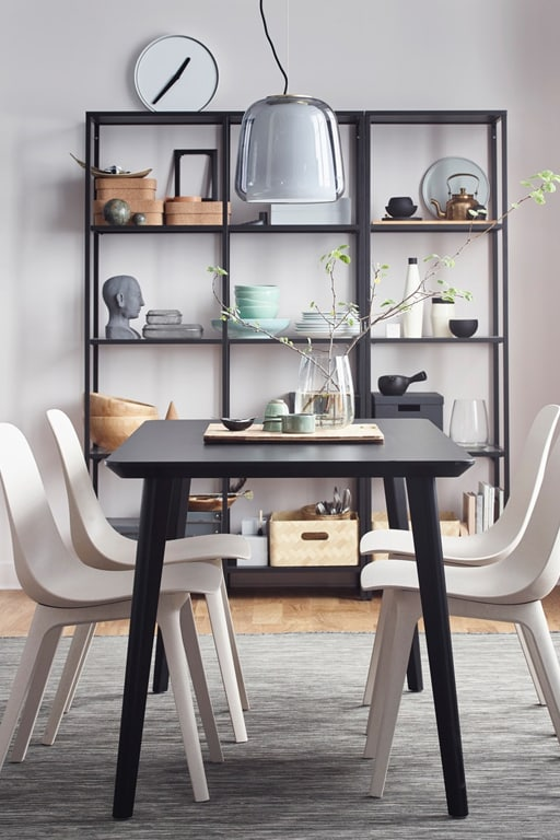 A dining room with dining storage shelves in the background.