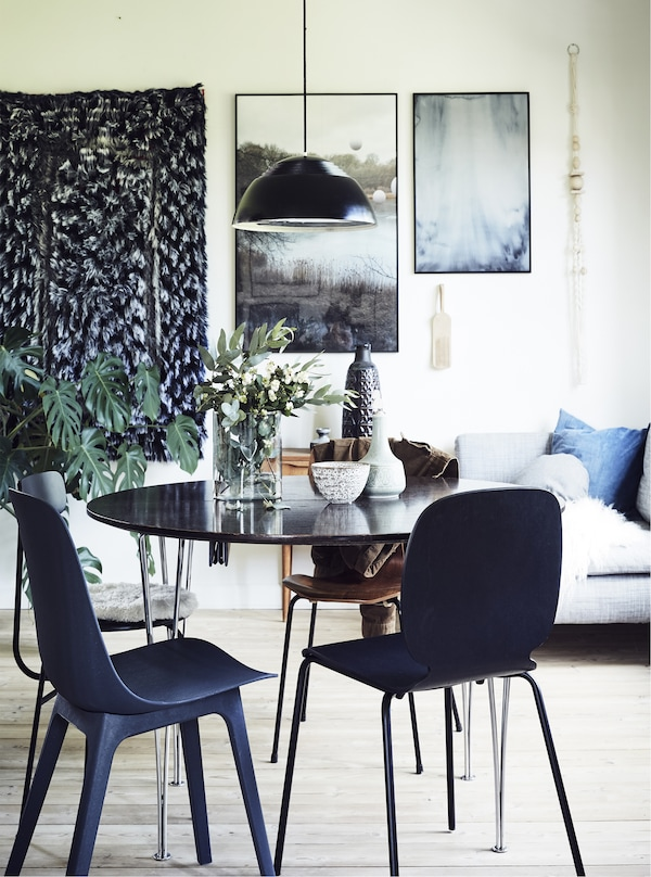 A dining room with pictures, wall hanging and pendant light.