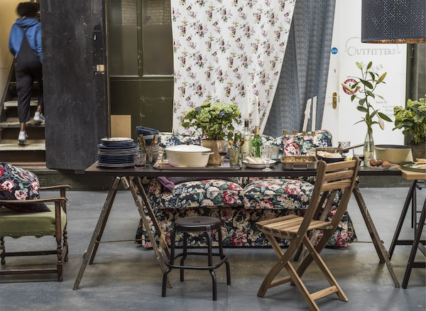 A dining space with mismatched chairs, potted plants and a floral sofa.