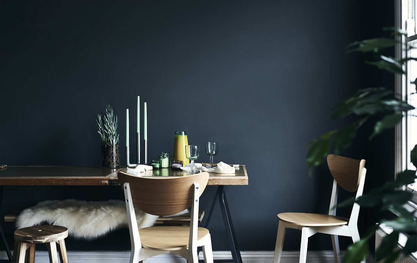 A dining table against a dark blue wall.