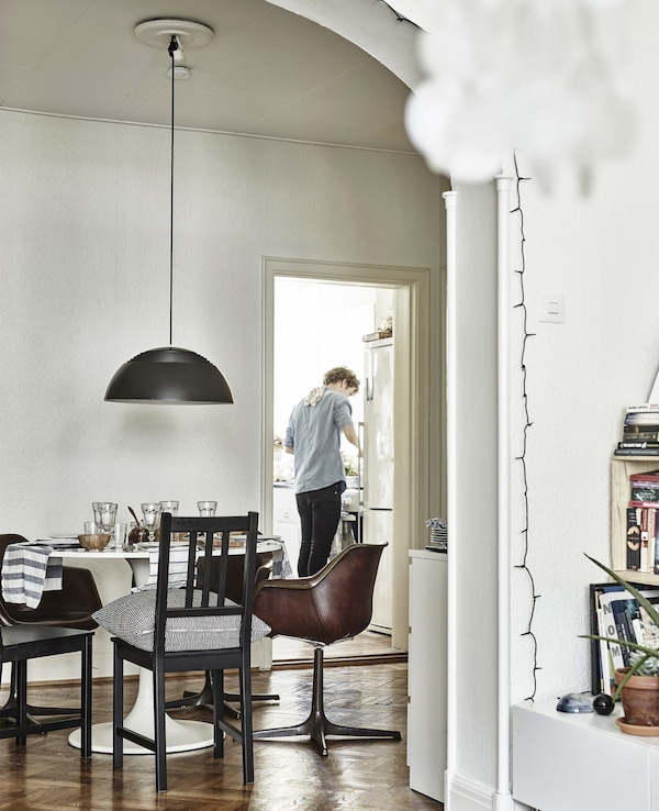 A dining table and chairs with a door through to a kitchen.