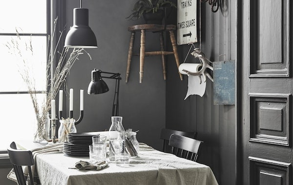 A dining table covered in a linen table cloth in a modern rustic kitchen with personal decor hanging on a wall