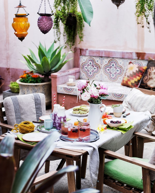 A dining table dressed with tableware, pink plants and glassware.