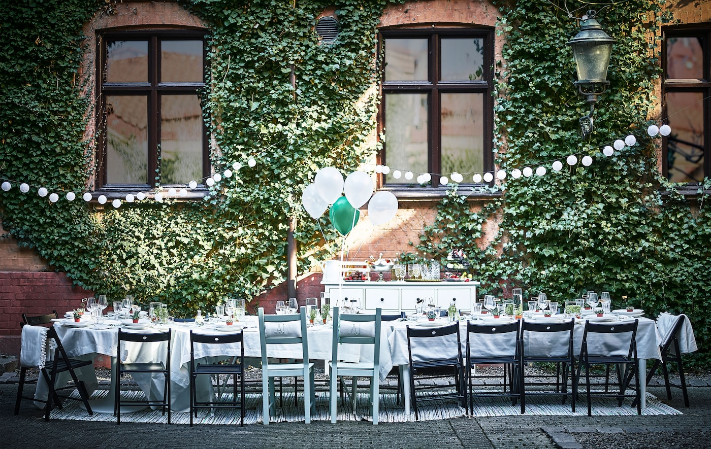 A dining table for a wedding is set up in a courtyard.