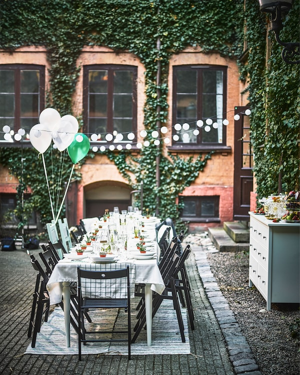 A dining table for a wedding is set up in a courtyard, along with a string of lights, rugs and a chest of drawers.