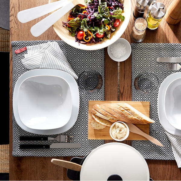 A dining table, plates and bowls in white, patterned place mats, cutlery and a salad from above.