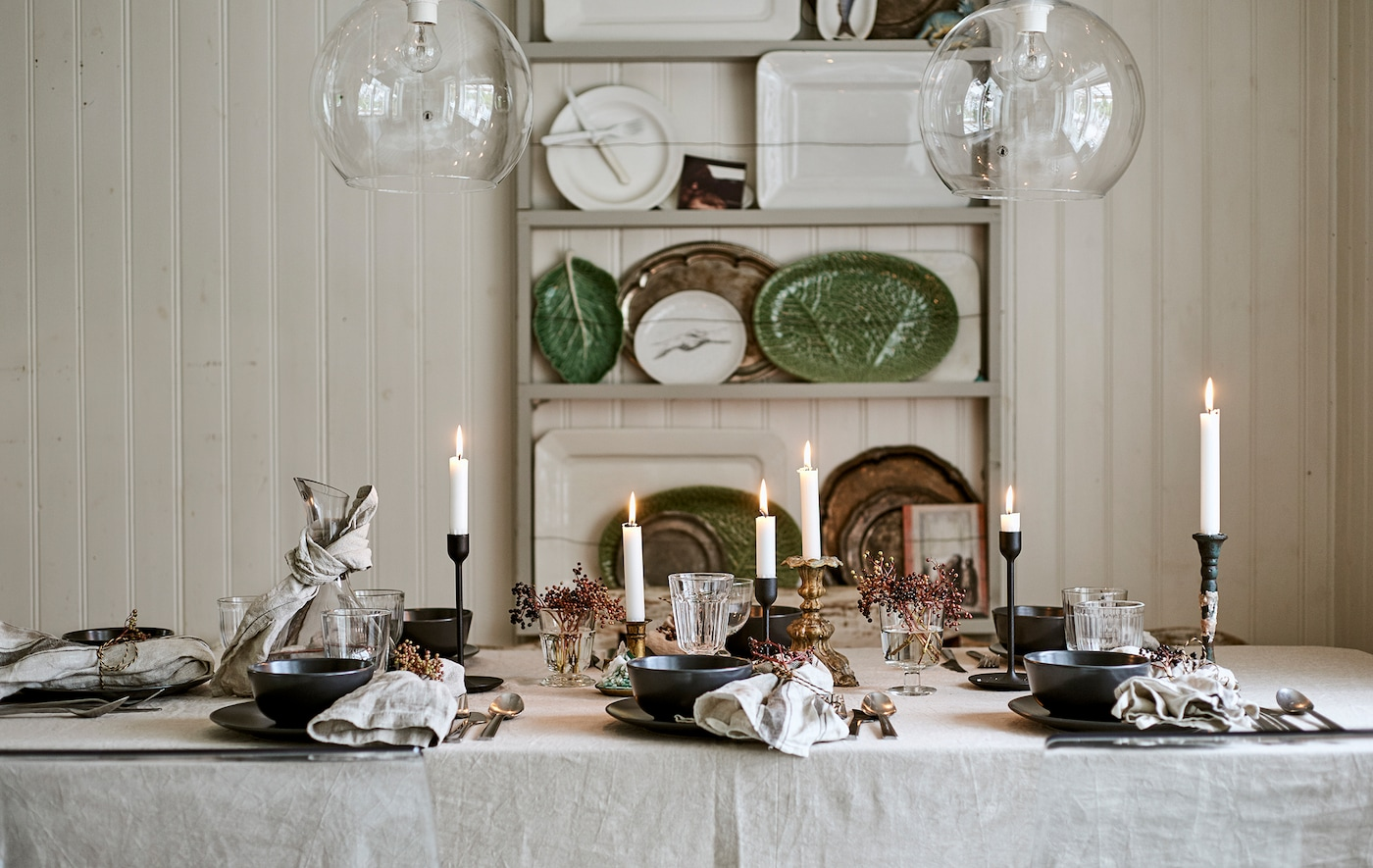 A dining table set for a festive meal with linen table cloth, candles, glassware and place settings with decorated napkins.