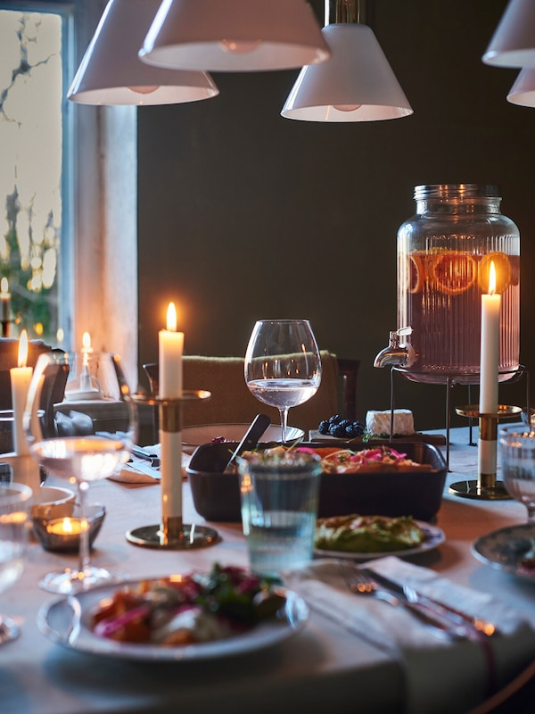 A dining table set for an informal meal with candlesticks, a beverage dispenser, pots and a roasting tin with tasty food.