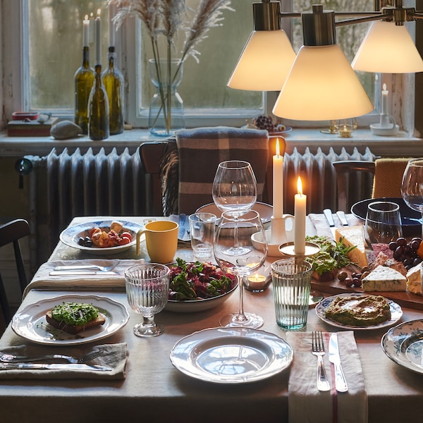 A dining table set with a monochrome tablecloth, kitchen towels as napkins and an informal mix of plates and glasses.
