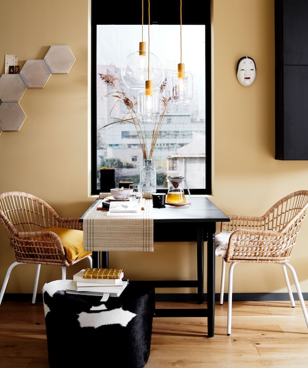 A dining table setup with two rattan chairs and a pouffe in front of a window, plus glass pendant light fittings.