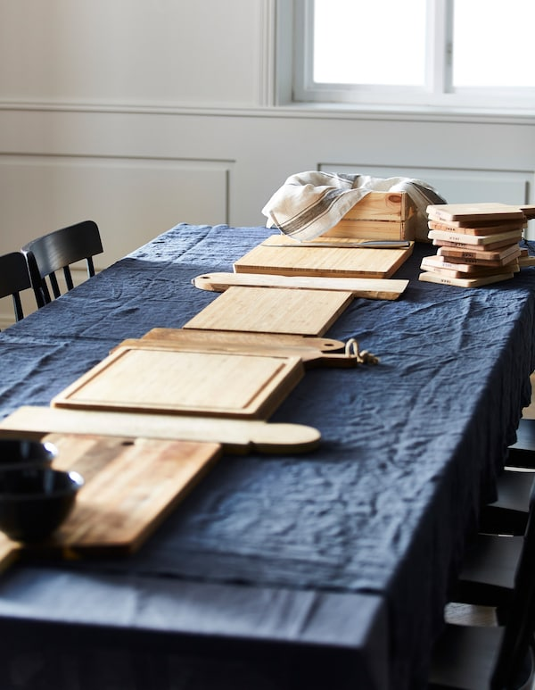 A dining table with a blue table cloth and chopping boards placed in a line down the middle.