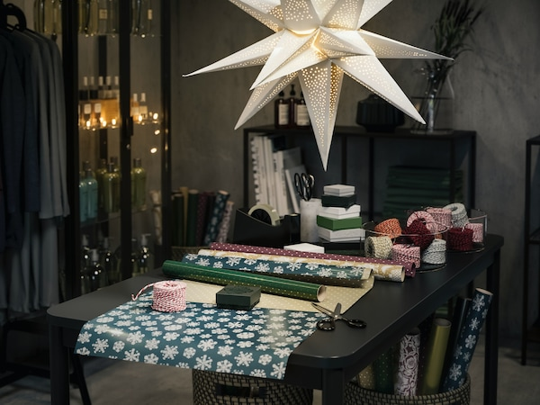 A dining table with a star hanging lamp above and table filled with beautiful wrapping paper and ribbon