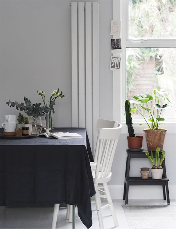 A dining table with dark tablecloth and white dining chairs.