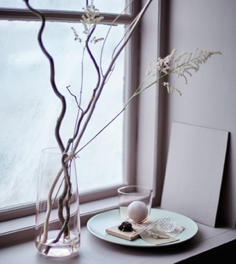 A display in a window with branches in a tall vase