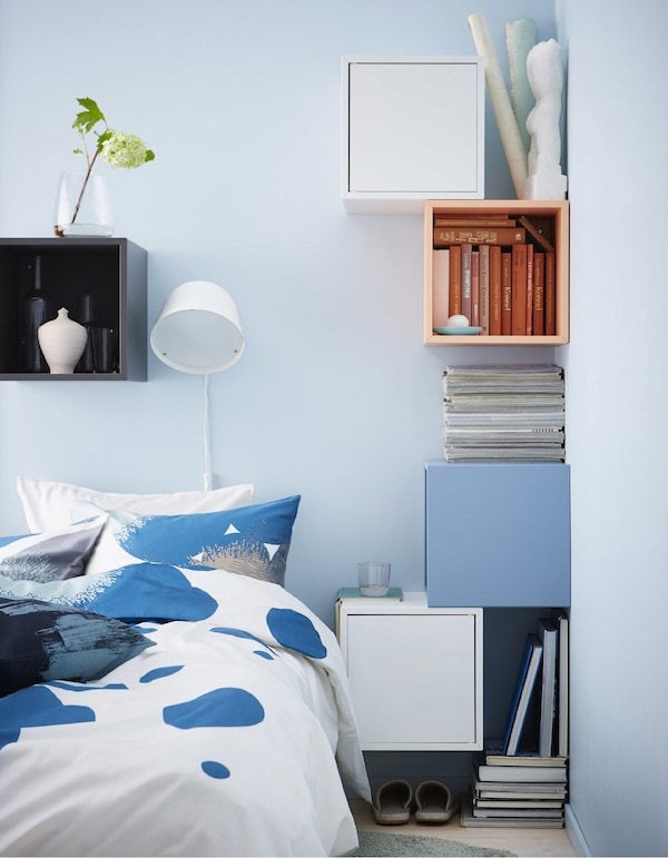 A DIY bedside table setup made from colourful cubic cabinets secured to the walls around a bed.